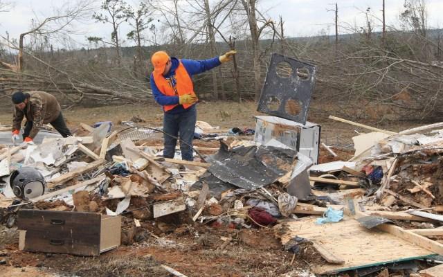 Trump expresa solidaridad a afectados por tornados en Alabama - Un residente busca artículos entre los escombros luego del paso del tornado que golpeó Beauregard, Alabama. Foto de Tami Chappell/AFP