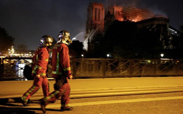 Relaciones Exteriores lamenta incendio en Catedral de Notre-Dame - Los bomberos observan el incendio en la histórica Catedral de Notre-Dame, en el centro de París, mientras cruzan un puente sobre el río Sena, el 15 de abril de 2019. Se produjo un incendio en la histórica Catedral de Notre-Dame, en el centro de París, que posiblemente involucra trabajos de renovación en el sitio, dijo el servicio de bomberos. Foto de GEOFFROY VAN DER HASSELT / AFP