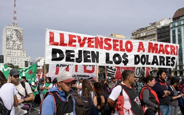 """""""Pagina quince: Argentina de mal en peor"""": Daniel Zovatto - Manifestantes de organizaciones sociales marchan a lo largo de la avenida 9 de Julio con un cartel que dice"""