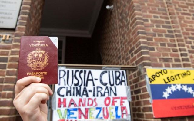 Venezuela exige a EE.UU. proteger su embajada en Washington - Ciudadana sostiene su pasaporte frente a la embajada de Venezuela en Washington DC. Foto de Nicholas Kamm