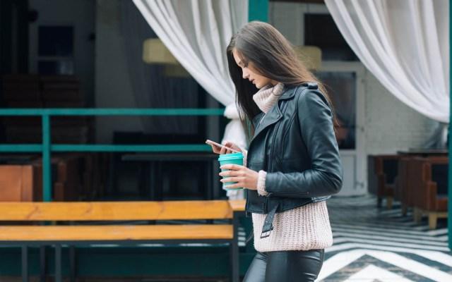Proponen multar a quienes caminen utilizando el celular en Nueva York - Mujer caminando con el celular en la mano. Foto de Photo Azat Satlykov / Unsplash