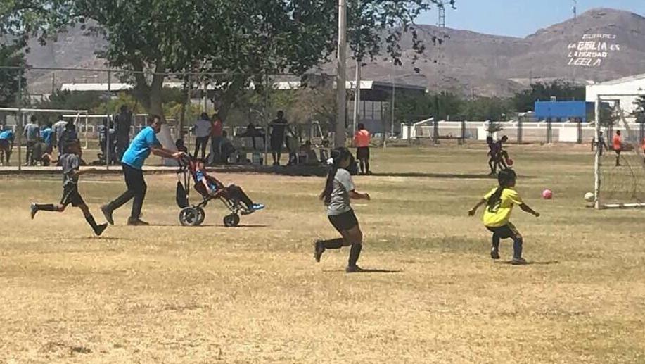 Padre empuja silla de ruedas de su hijo para que juegue futbol en Chihuahua - Foto de OmarFdoRubio