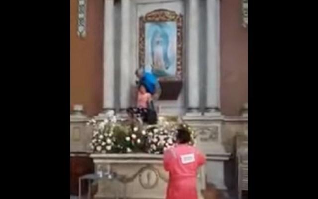 #Video Mujer ataca cuadro de la virgen por segunda vez en Tampico - La mujer fue retenida por un feligrés al atacar cuadro. Captura de pantalla