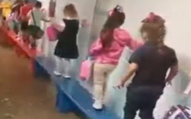 #Video Crean puente con bancos para evacuar escuela inundada en Houston - Alumnos caminando en el puente de bancos. Captura de pantalla