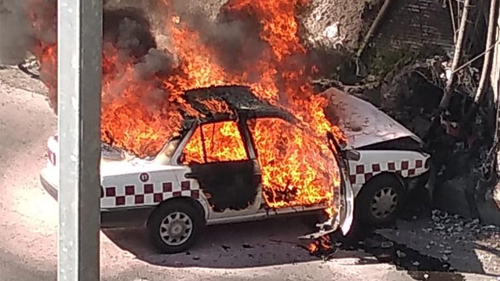 Taxi quemándose tras choque en la México-Querétaro. Foto de @CoordinacionDM