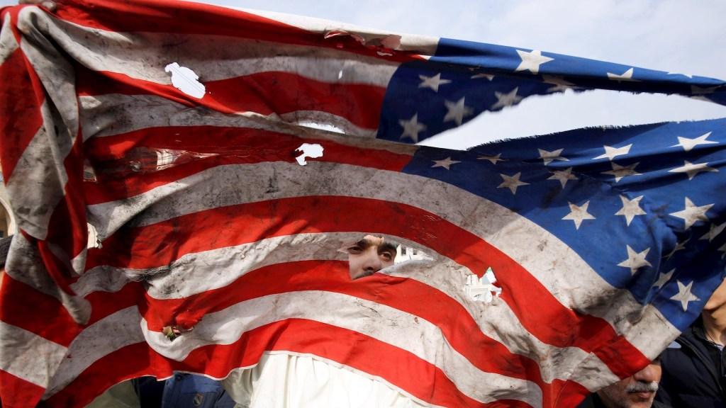 EE.UU. restringe entrada a alto cargo de Guardia Revolucionaria iraní - Manifestante rompe una bandera estadounidense durante una manifestación multitudinaria contra EEUU, este viernes en Teherán, después de que el Pentágono reivindicase el bombardeo selectivo que acabó con la vida del comandante de la Fuerza Quds de los Guardianes de la Revolución de Irán, Qasem Soleimaní, en los aledaños del aeropuerto de Bagdad (Irak). Foto de EFE/Abedin Taherkenareh.