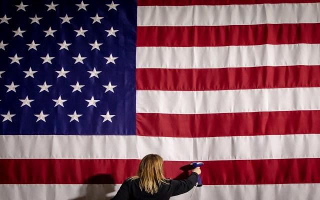 """Iowa amanece sin resultados y Trump critica """"desastre total"""" de demócratas - Amy Pfeiffer, asistente ejecutiva de la firma Production Management One, plancha este lunes una bandera estadounidense previo al acto organizado por el precandidato Pete Buttigieg para esperar los resultados del primer caucus del Partido Demócrata en Des Moines, Iowa. Foto de EFE/GARY HE."""