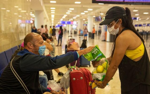 Mexicanos ayudan con víveres a extranjeros varados en aeropuerto de Cancún - Una mujer regala manzanas a un turista en el aeropuerto internacional de Cancún, Quintana RooUna mujer regala manzanas a un turista en el aeropuerto internacional de Cancún, Quintana Roo
