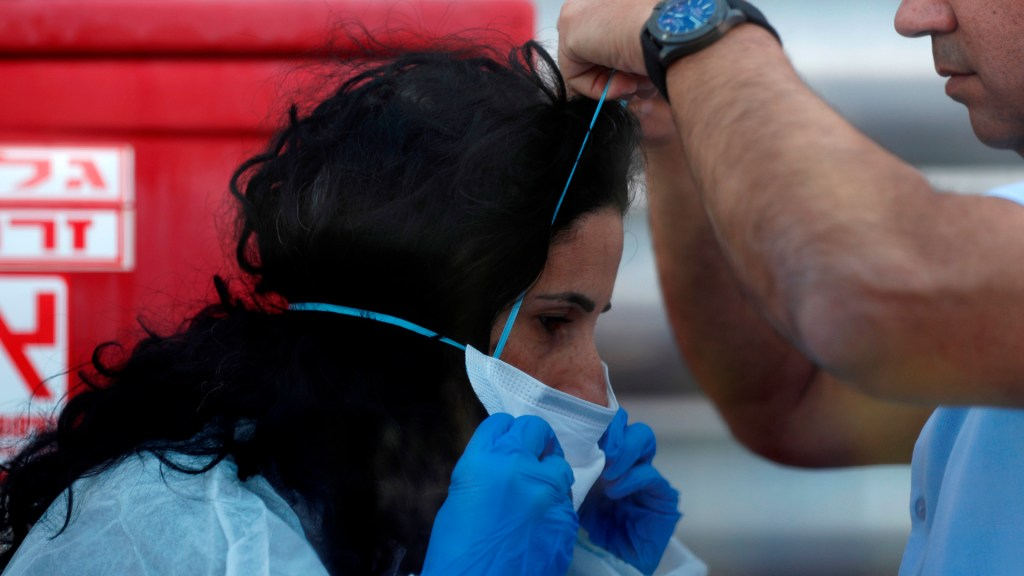 FMI cuenta con 50 mmdd para hacer frente al coronavirus - Mujer colocándose cubrebocas para evitar contagio de coronavirus. Foto de EFE