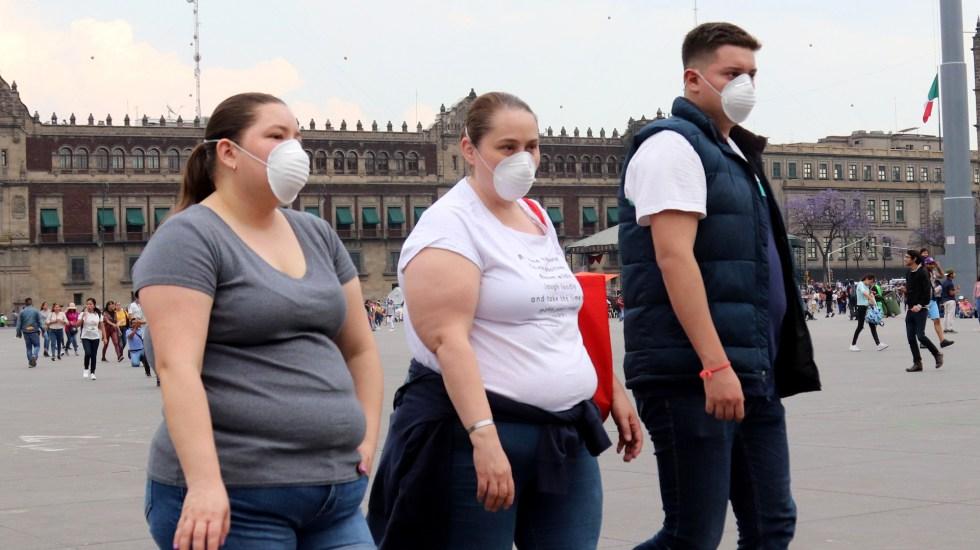 Emiten acuerdo para establecer medidas preventivas ante el coronavirus - Peatones con cubrebocas en el Zócalo de la Ciudad de México. Foto de EFE
