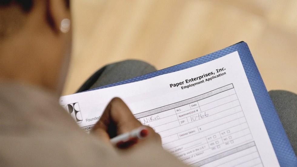 COVID-19 dispara peticiones de desempleo en EE.UU. a 3.28 millones - Hombre llena una planilla de trabajo en un centro comunitario de Nueva York. Foto de EFE