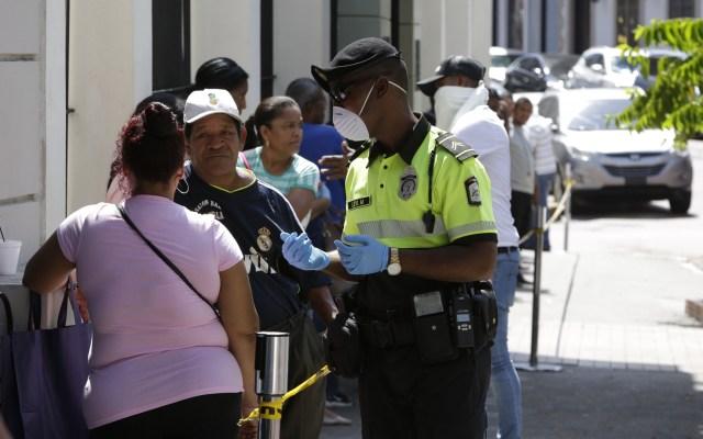Panamá suma 786 contagios de COVID-19 y 14 muertes - Un policía controla la fila de decenas de personas para comprar billetes de lotería, acción que desafía las medidas de seguridad y no aglomeración en Ciudad de Panamá. Foto de EFE