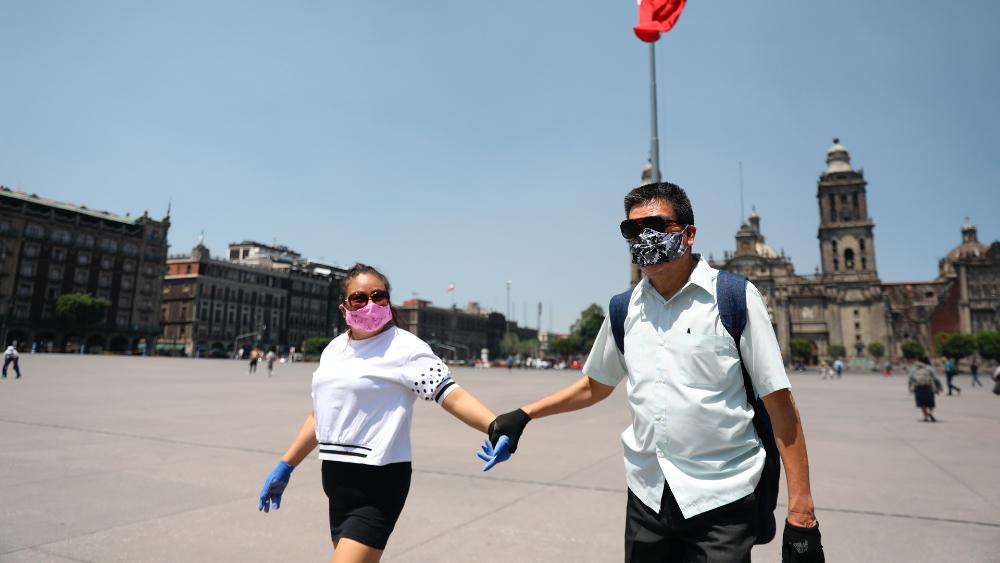 Convocará AMLO a besos y abrazos en el Zócalo cuando acabe emergencia por COVID-19 - Pareja pasea con cubrebocas pro el Zócalo de la CDMX. Foto de EFE