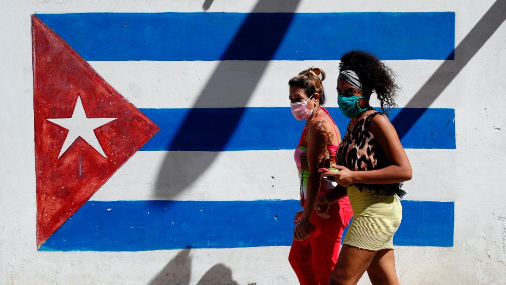 EE.UU. no busca eliminar remesas a Cuba sino el lucro a costa de la necesidad - En la imagen, dos personas caminan con cubrebocas con la bandera de Cuba pintada de fondo. Foto de EFE