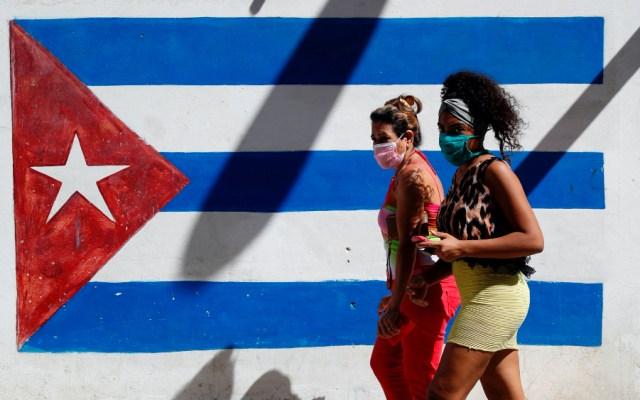 Biden y Harris derogarán la política de Trump a Cuba, pero el bloqueo seguirá - En la imagen, dos personas caminan con cubrebocas con la bandera de Cuba pintada de fondo. Foto de EFE