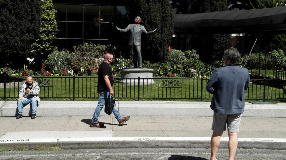 Distanciamiento social por COVID-19 en EE.UU. continuará todo el verano - Estadounidenses pasean frente a estatua de Tony Bennett con cubrebocas. Foto de EFE