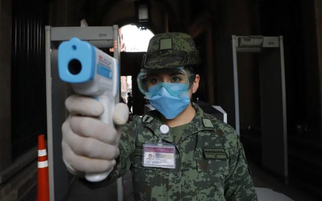 En el Ejército no hay muertos por coronavirus, contagiados sí - Militar toma la temperatura a quienes ingresan a Palacio Nacional para detectar COVID-19. Foto de Notimex