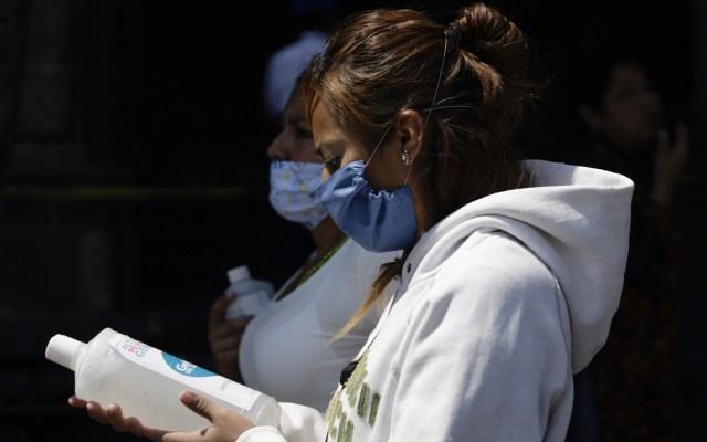 Muere en Tlaxcala una segunda persona por COVID-19 - Mujer en calles de la CDMX con botella de gel antibacterial. Foto de Notimex
