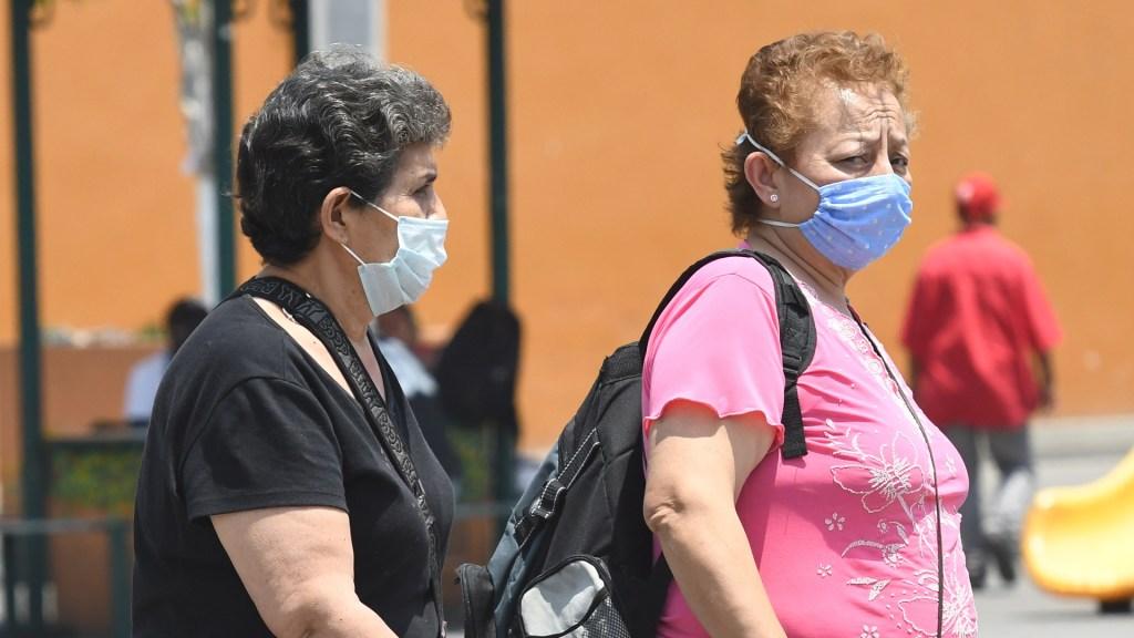 En México, mujeres trabajan 6.2 horas más a la semana que los hombres - Mujeres con cubrebocas en calles de México. Foto de EFE