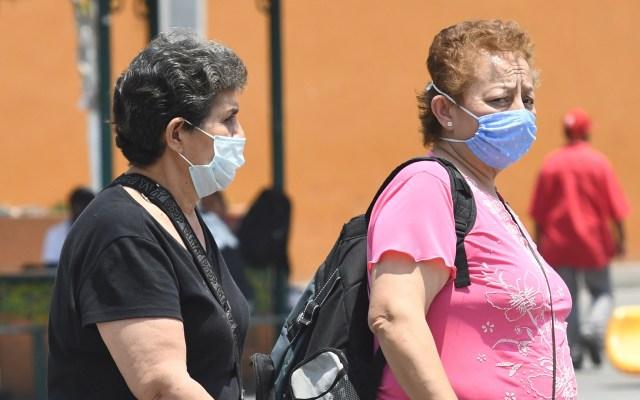 Piden a AMLO liderar pacto nacional para superar crisis del COVID-19 - Mujeres con cubrebocas en calles de México. Foto de EFE