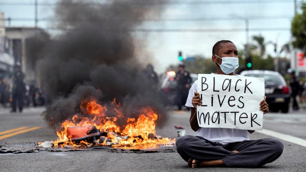Fiscal de Minnesota valida que afroamericanos teman a la Policía - Manifestante contra muerte de George Floyd sostiene pancarta que afirma que 'las vidas de los negros importan'. Foto de EFE