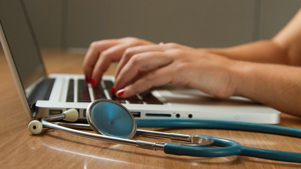 COVID-19 plantea el reto de digitalizar los sistemas de salud - Profesional de la salud en computadora. Foto de National Cancer Institute / Unsplash