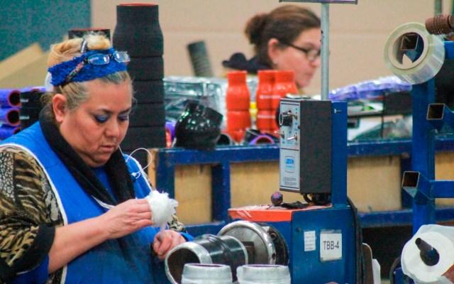 COVID-19 hunde el PIB de una economía mexicana que ya estaba enferma - Foto de persona mientras trabaja en una maquiladora, en Tijuana. Foto de EFE/ Archivo.