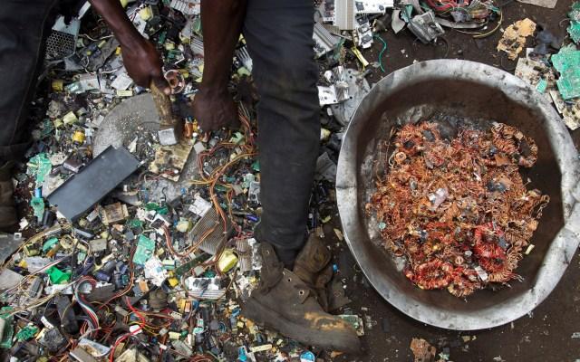 El 2019 alcanzó cifra récord en generación de basura electrónica - Un hombre rescata hilos de cobre de entre restos de aparatos tecnológicos en un vertedero. Foto de EFE