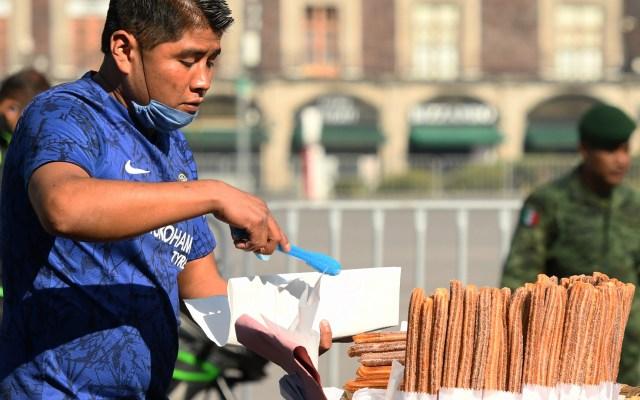 Más de 15 millones de mexicanos sin empleo en medio de la pandemia - Hombre vende churros en el Zócalo de la Ciudad de México. Foto de EFE