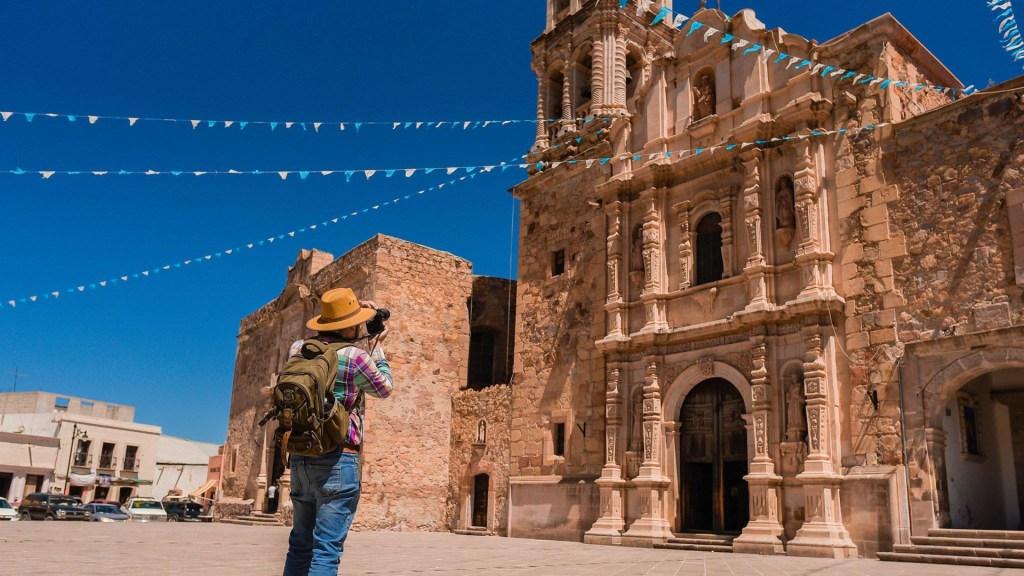 Presenta Sectur nueva versión de la plataforma Visit Mexico - Hombre toma foto a iglesia en destino turístico de México. Foto de @SECTUR.MX