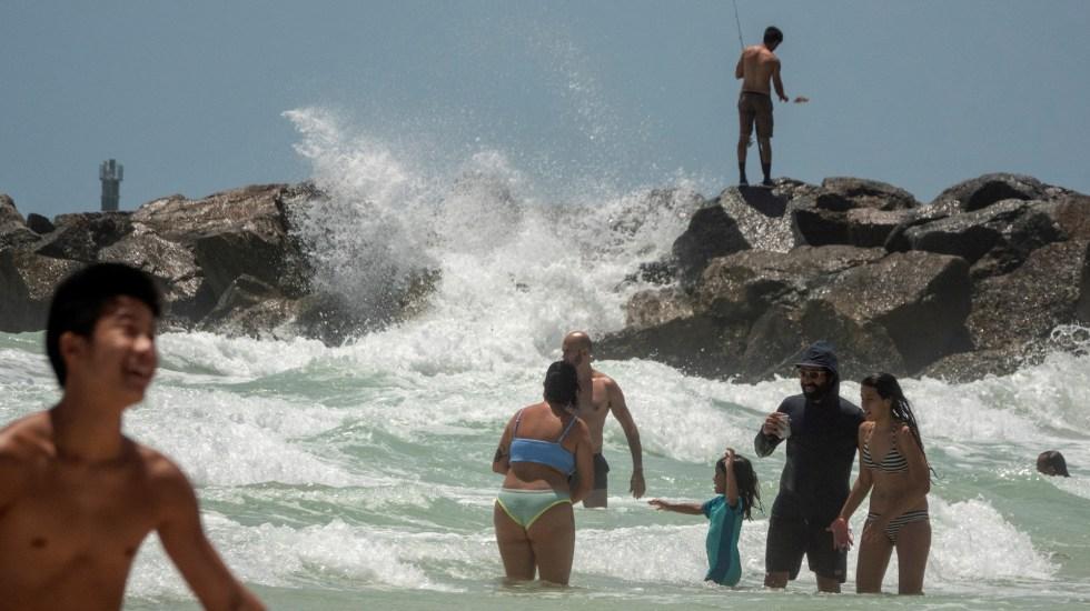 Isaías se debilita antes de impactar la costa este de Florida - Personas en Florida disfrutan de la playa antes de la llegada de Isaías. Foto de EFE