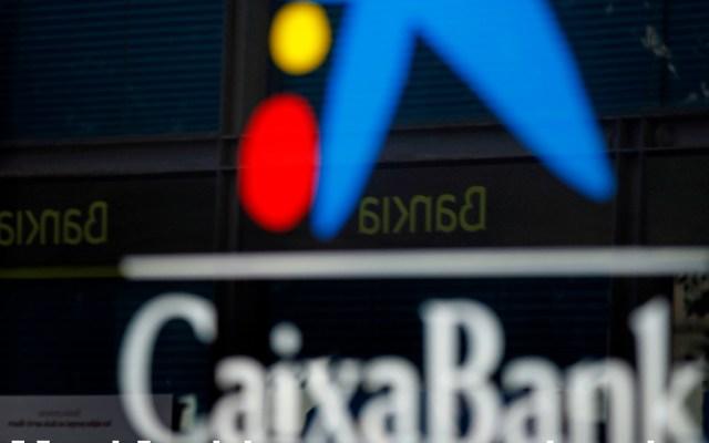 CaixaBank y Bankia dan luz verde a crear el primer banco en España - Vista de una oficina de CaixaBank y otra de Bankia reflejada en el cristal en el centro de L'Hospitalet, en Barcelona. Foto de EFE