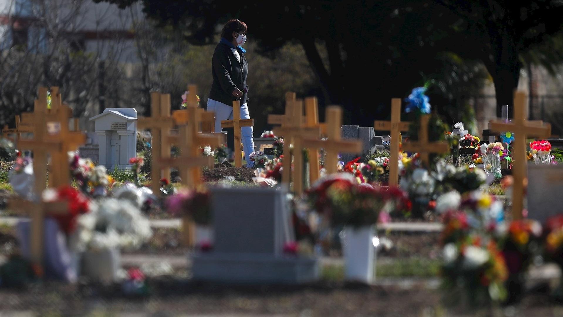 Una mujer camina frente a unas cruces en un cementerio de Buenos Aires, Argentina. Foto de EFE/Juan Ignacio Roncoroni.