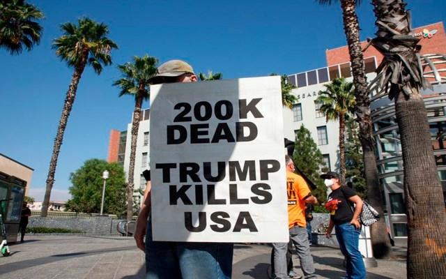 EE.UU. a horas de rebasar las 200 mil muertes por COVID-19; uno de cada cinco defunciones en el mundo ocurren en ese país - Un manifestante sostiene un cartel durante una manifestación en Los Ángeles, California, contra el presidente Donald Trump. Estados Unidos casi alcanza los 200 mil muertos por la pandemia de COVID-19. Foto Agencia EFE