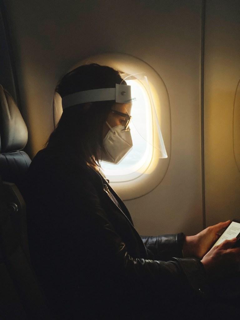 Segunda ola de la pandemia vuelve a hundir la demanda aérea un 70 % - Pasajera de avión con careta y cubrebocas. Foto de Camila Perez / Unsplash