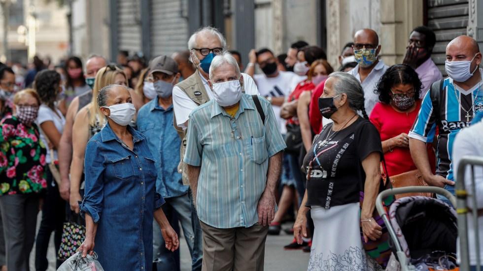 OMS atribuye pandemia de COVID-19 al cambio climático - Personas en Brasil con cubrebocas para evitar el COVID-19. Foto de EFE