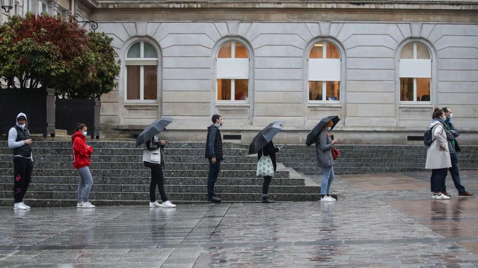 Aumento generalizado de contagios y medidas por COVID-19 en toda Europa - Fila en la lluvia para realizarse prueba de coronavirus en Francia. Foto de EFE