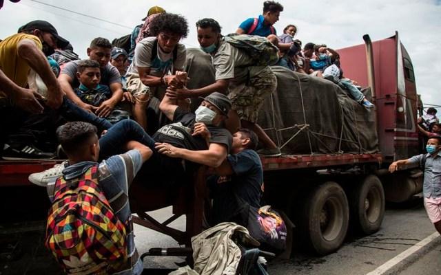Improbable que migrantes hondureños representen un problema de salud en México: López-Gatell - Migrantes ayudan al hondureño Wilmer, de 32 años y quien utiliza silla de ruedas para moverse, a subirse a la plataforma de un transporte pesado para avanzar por la carretera hacia México, hoy en Río Dulce (Guatemala). Cientos de hondureños que conformaron una nueva caravana de migrantes caminan por territorio guatemalteco con Estados Unidos como su destino final. EFE/Esteban Biba