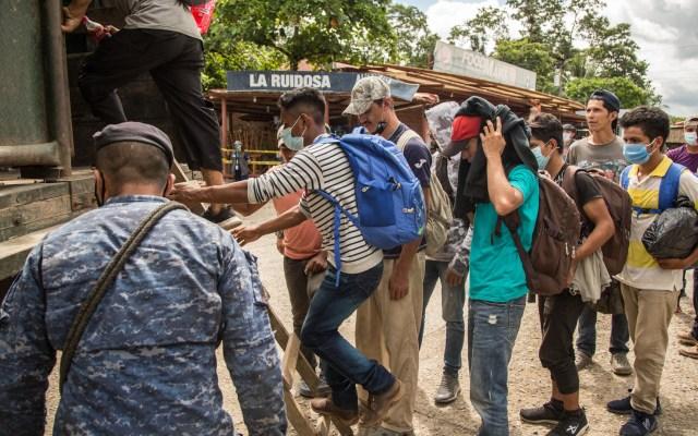 Pandemia de COVID-19 frenó caravana migrante de Honduras, reafirma Ebrard - Migrantes suben a un camión del Ejército de Guatemala que los regresaría a la frontera entre Honduras y Guatemala. Foto de EFE