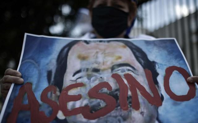 Nicaragüenses se manifiestan en Costa Rica contra Daniel Ortega - Mujer muestra cartel con la imagen del presidente nicaragüense, Daniel Ortega, y la palabra