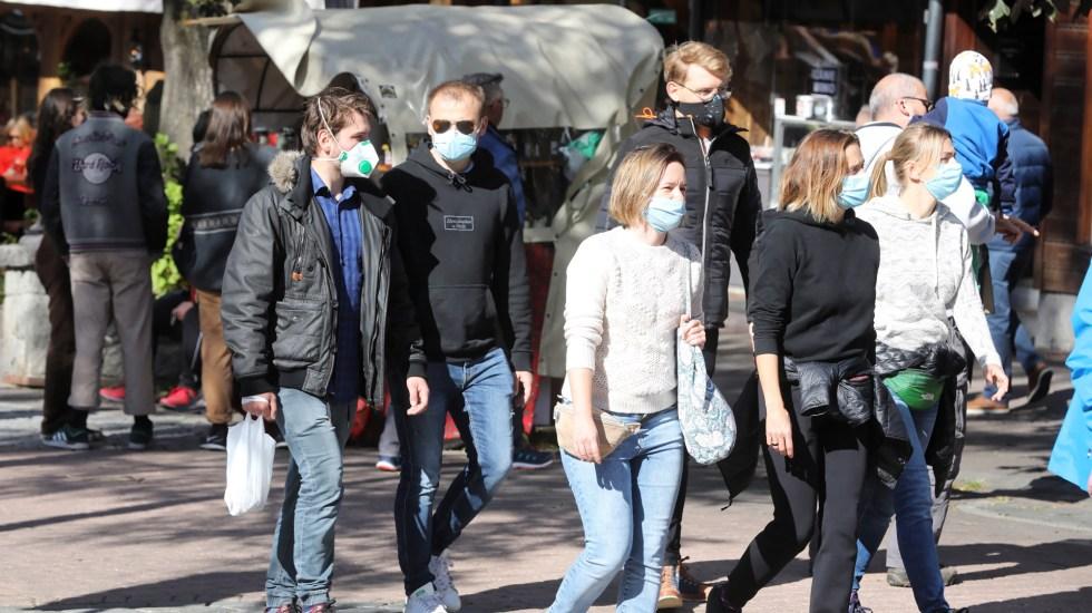 Se elevan en el mundo a un millón 30 mil 160 los muertos por COVID-19 - Transeúntes en Polonia con cubrebocas. Foto de EFE