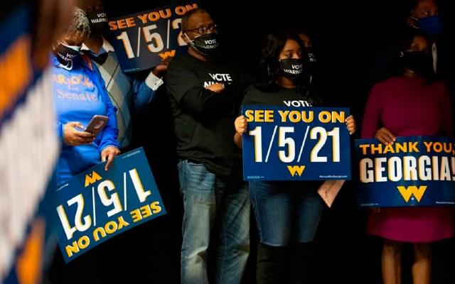 La silenciosa espera de los resultados presidenciales en Estados Unidos - Simpatizantes en Atlanta sostienen carteles mientras el candidato demócrata al Senado de Estado Unidos, Raphael Warnock, habla durante un evento de la noche de elecciones en Georgia. EFE/ EPA/Jessica McGowan/POOL