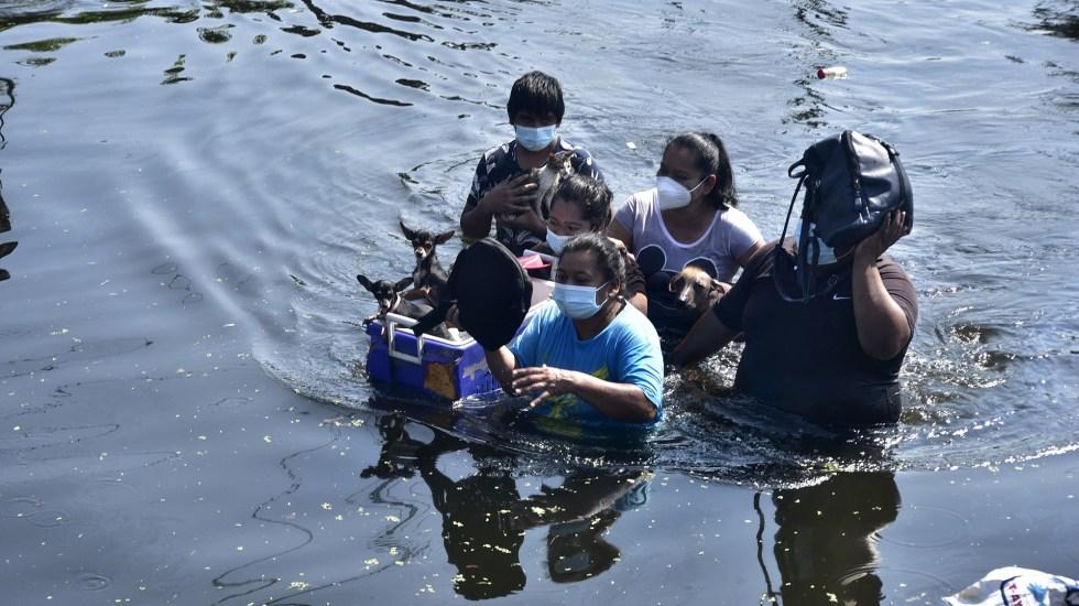 'Criminal' la falta de previsión de lluvias en el sureste de México, critica Alfonso Romo - Familia atraviesa inundaciones en Villahermosa, Tabasco. Foto de EFE