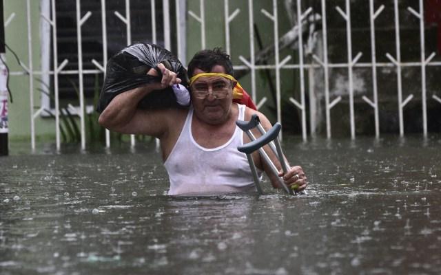Lluvias por Frente Frío 9 en México marcaron récord histórico - Hombre rescata pertenencias en inundación por lluvias en Villahermosa, Tabasco. Foto de EFE