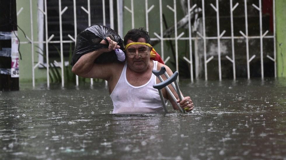Oficializan en DOF desaparición del Fonden - Hombre rescata pertenencias en inundación por lluvias en Villahermosa, Tabasco. Foto de EFE