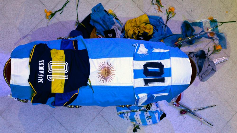 Empleados de funeraria se toman fotos junto al cuerpo de Maradona - Foto de EFE