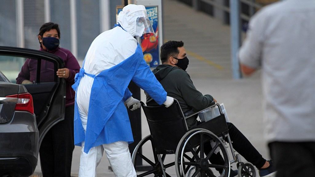 Aprueba Congreso de Chihuahua uso obligatorio de cubrebocas para enfrentar COVID-19 - Trabajador sanitario empuja la silla de ruedas con un paciente presuntamente positivo a COVID-19 a su ingreso  al hospital General de Ciudad Juárez, Chihuahua. Foto de EFE