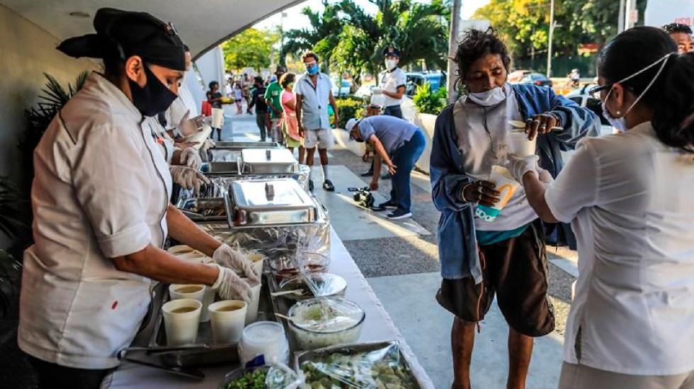Trabajadores de hotel reparten cenas a personas de bajos recursos por Año Nuevo en Acapulco - Empleados del hotel Krystal Beach reparten cenas calientes a personas de bajos recursos en el puerto de Acapulco. Foto EFE