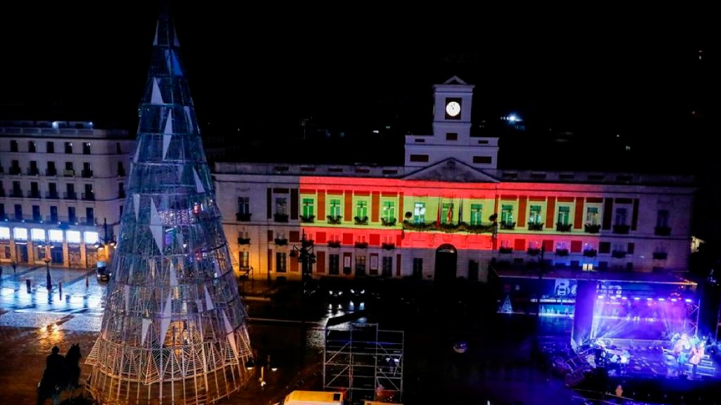 Sin festejos, COVID-19 obliga en el mundo a recibir Año Nuevo con muchas restricciones - La bandera de España es proyectada sobre la fachada de la sede del gobierno de la Comunidad de Madrid, en la plaza de la Puerta del Sol de Madrid vacía. Foto EFE
