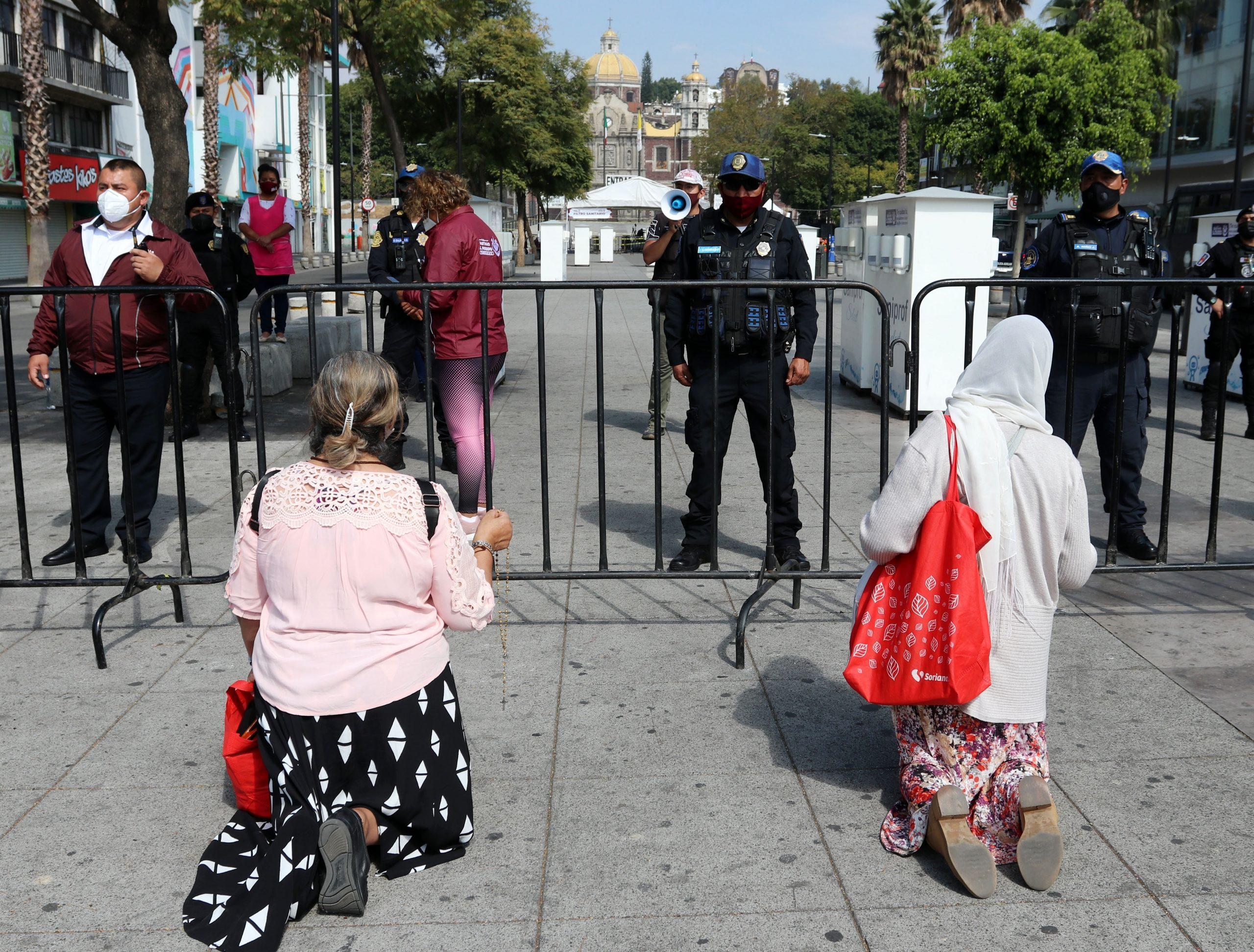 Personas rezan hoy, afuera de la Basílica de Guadalupe de Ciudad de México. Foto de EFE/José Pazos.
